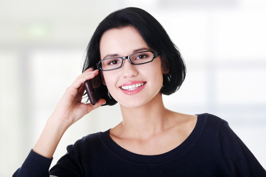 girl smiling while talking to her phone
