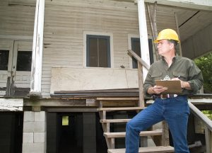 man inspecting old house