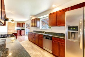 long kitchen with wood cabinets and other kitchen appliances