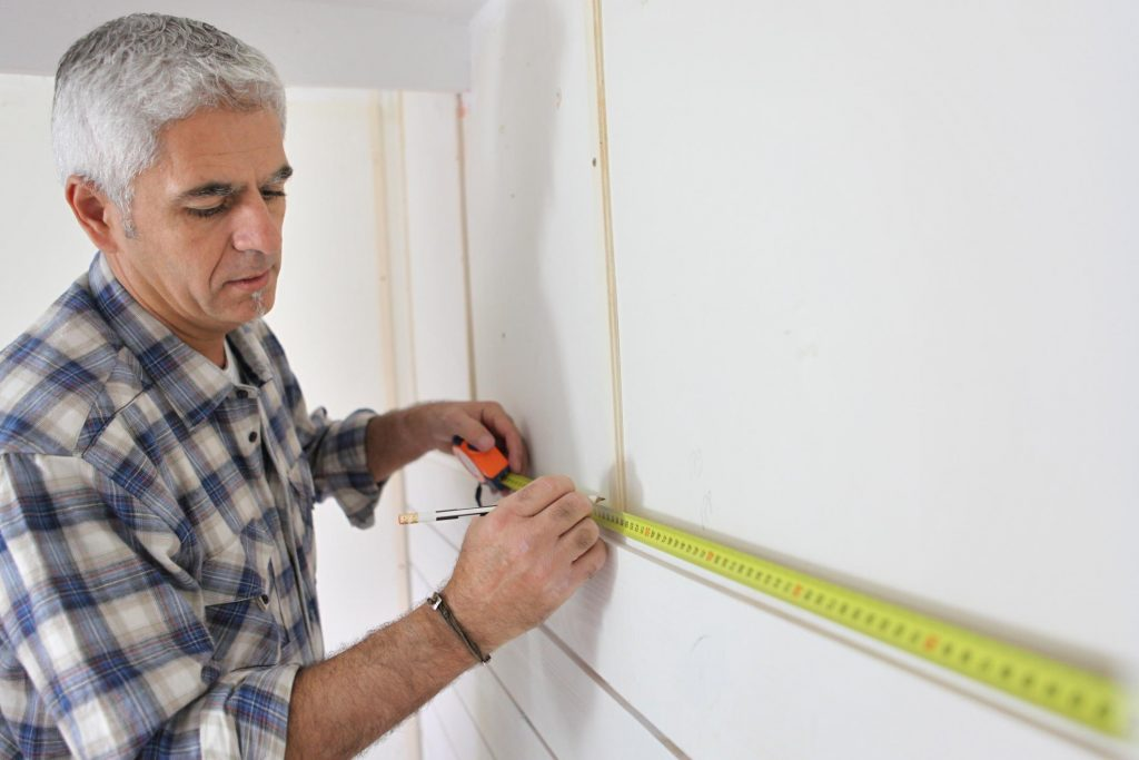 old man measuring the wall